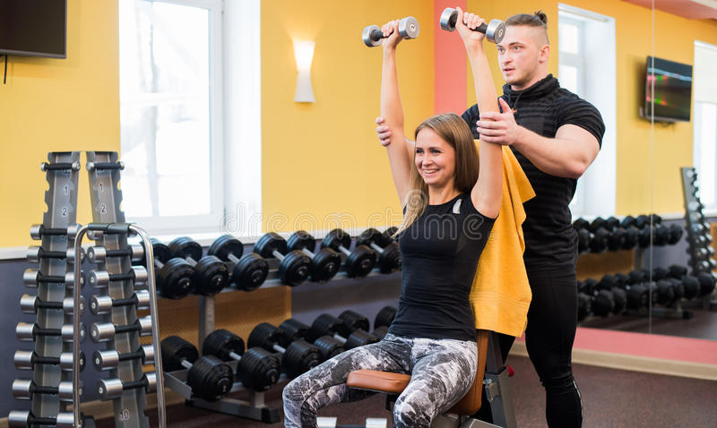解决在健身房:做哑铃锻炼的美丽的yong妇女坐长凳,当观看肌肉的教练员和时 库存照片