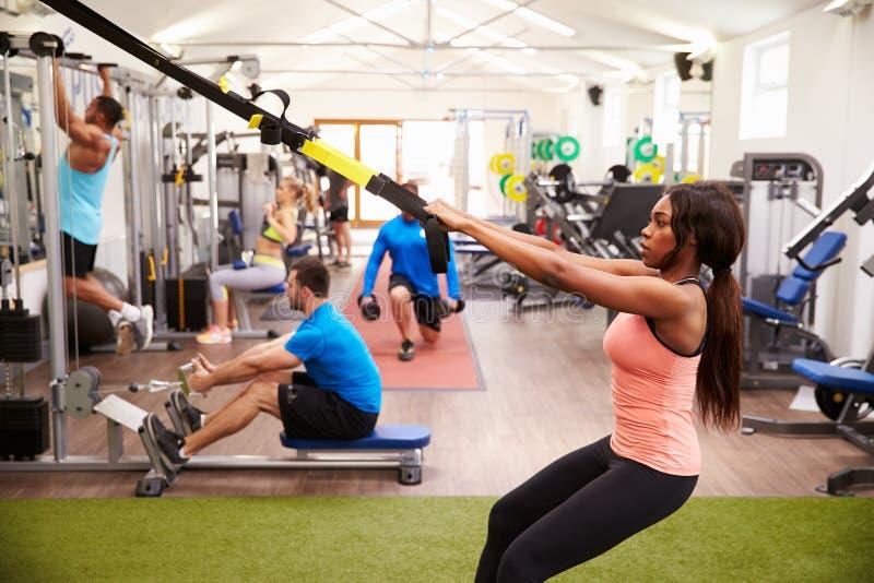 解决在健身设备的人们在一间繁忙的健身房 免版税库存照片