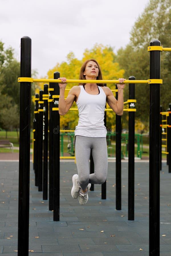 解决在室外健身房的年轻运动健身妇女做引体向上在日出 免版税库存图片