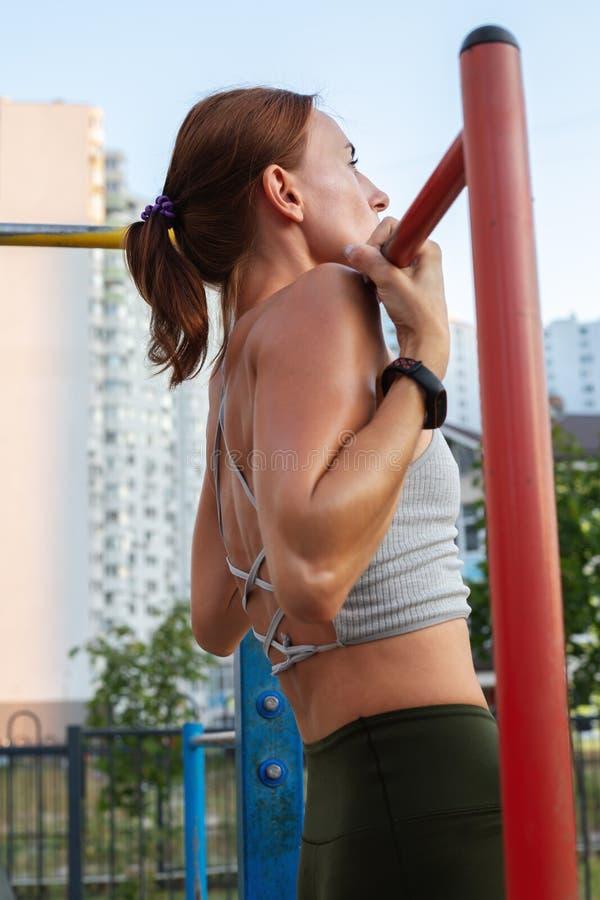 解决在室外健身房的运动健身妇女做引体向上 免版税图库摄影