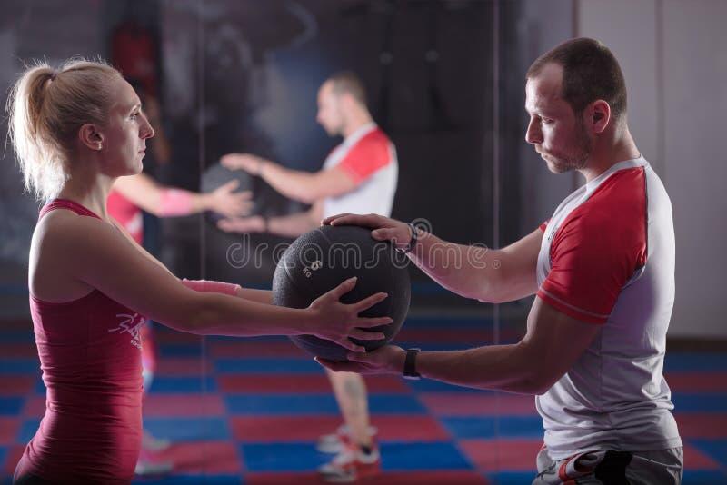 解决在对,解决在与个人教练员的健身房 帮助与疏松重量,训练在对 免版税库存图片