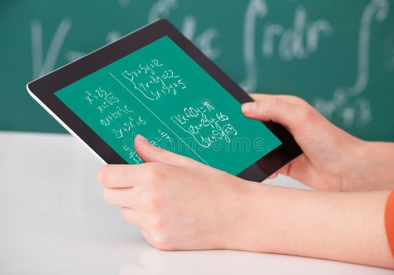 解决在数字式片剂的学生数学题在教室 免版税库存图片