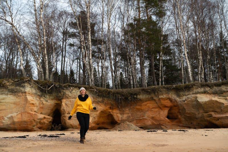解决在海滩的愉快的体育和时尚恋人热心者穿明亮的黄色毛线衣和黑手套和盖帽 免版税库存照片