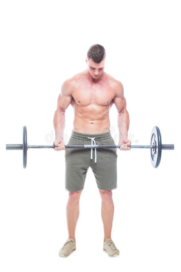 解决在演播室的肌肉人做与杠铃的锻炼在二头肌,强的男性赤裸躯干吸收 ??  免版税库存照片