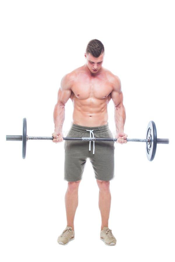 解决在演播室的肌肉人做与杠铃的锻炼在二头肌,强的男性赤裸躯干吸收 ??  免版税库存图片