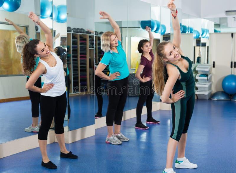 解决在现代健身房的有氧类的正面女性 免版税库存照片