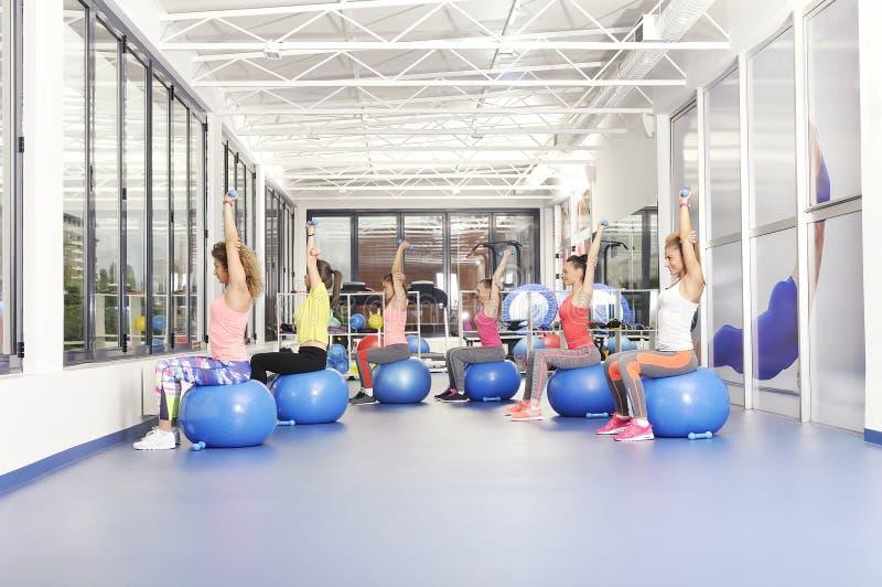 解决在蓝色pilates球的小组美丽的少妇 库存照片