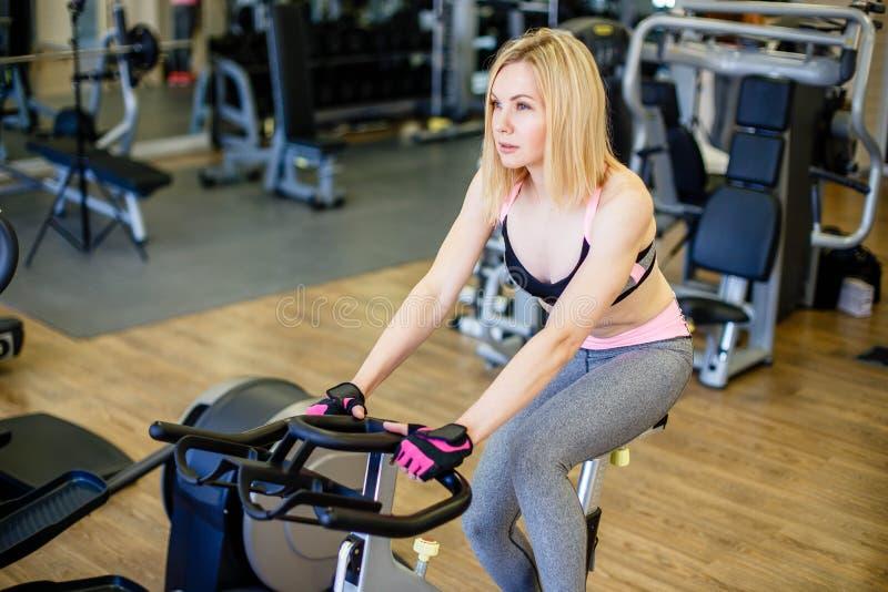 解决在锻炼脚踏车的适合的妇女在健身房 女性做的健身训练的室内射击在转动的自行车的在健康分类 免版税库存照片