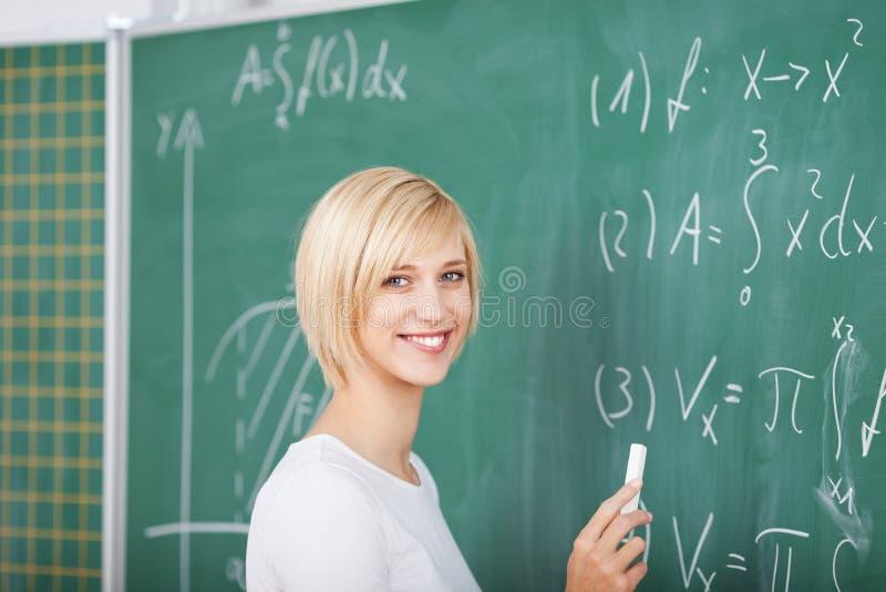 解决在黑板的女学生总和在教室 库存照片