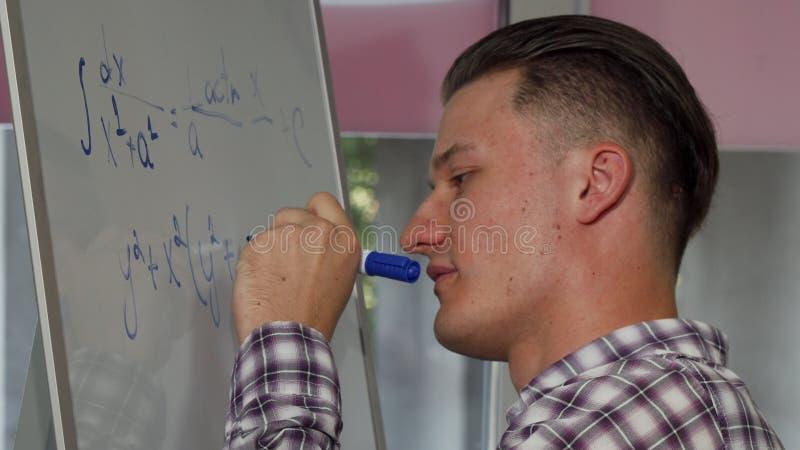解决在whiteboard的英俊的年轻人数学问题 免版税库存照片