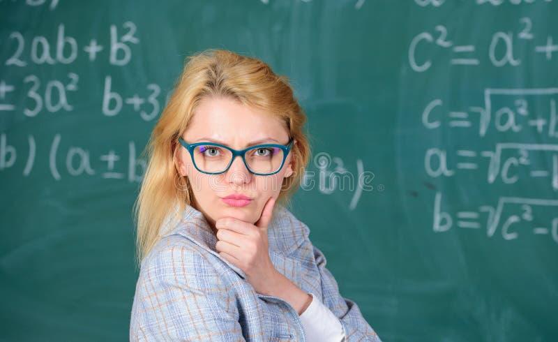 解决数学任务 老师妇女考虑解决和结果 夫人穿戴镜片聪明的老师教室 库存照片