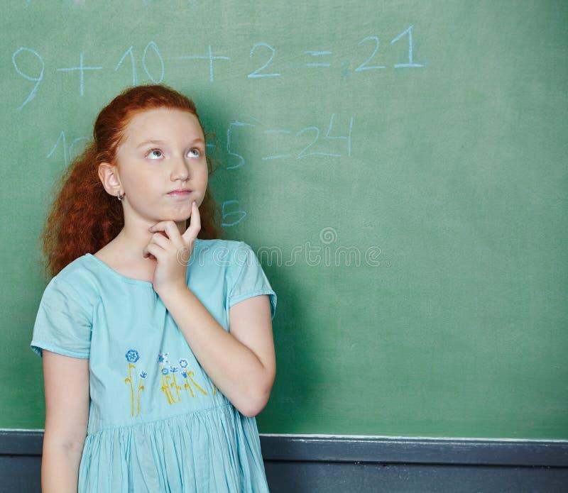 解决数学题的女孩在学校 免版税库存照片
