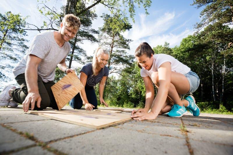 解决木板条难题的愉快的男性和女性朋友 免版税库存照片