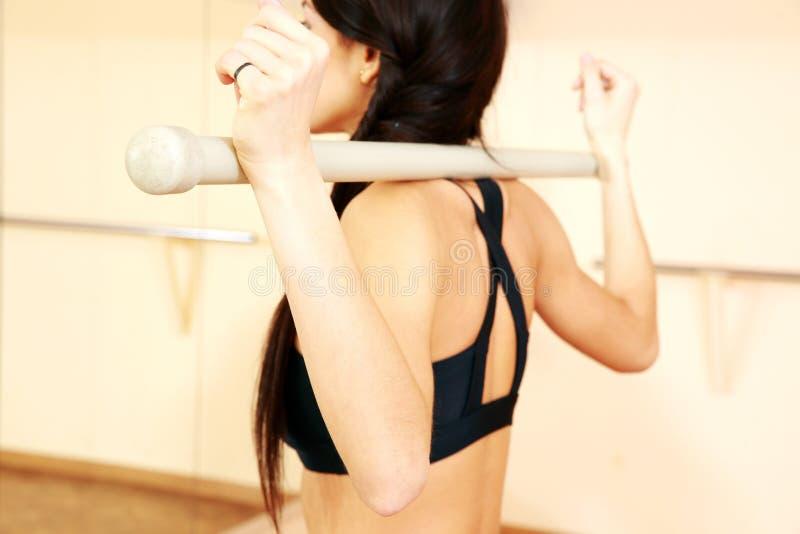 解决用体操棍子的年轻人适合的妇女 库存图片
