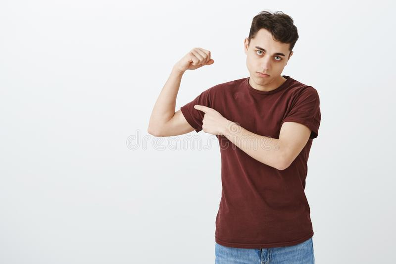 解决的人,但是微弱 阴沉的生气的英俊的人画象红色T恤杉举的胳膊和显示二头肌的 免版税库存照片