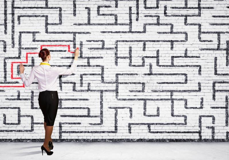 解决迷宫问题的女实业家 免版税库存照片