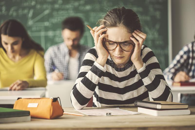 解决问题的学生在黑板后的教室测验 库存图片