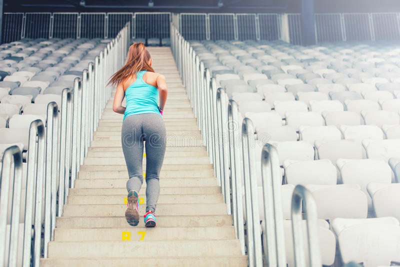 解决活跃女性的赛跑者享受锻炼,训练和 跑步在台阶的健身女孩 免版税库存照片