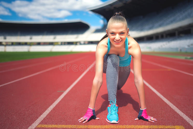 解决活跃母的赛跑者为轨道比赛做准备,享受锻炼,训练和 跑步在体育场的健身女孩 库存照片