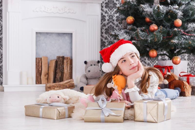 解开圣诞节礼物的圣诞老人帽子的美丽的女孩 免版税库存图片