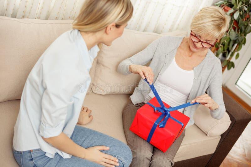 解开她从她的女儿接受了的礼物盒的母亲 库存照片