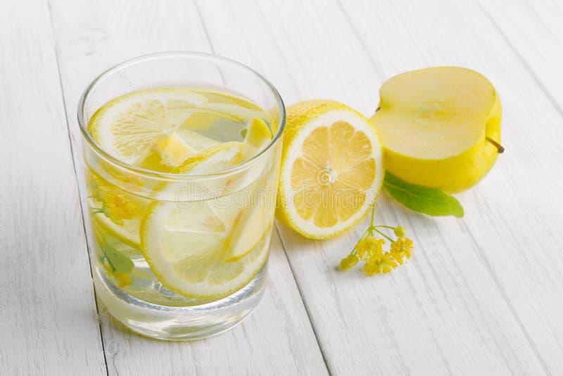 解毒的刷新的饮料,在玻璃,新鲜的苹果的柠檬水和在一张白色桌上的黄色菩提树花 库存照片