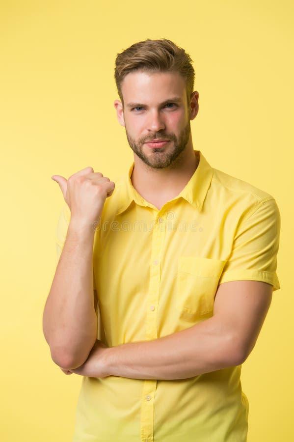 解答在这里 保留在下巴的英俊的年轻人手,当立场黄色背景时 难题 道德问题 免版税库存照片