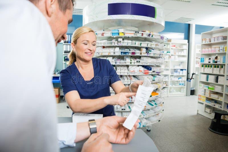 解释产品的细节药剂师对顾客 免版税图库摄影