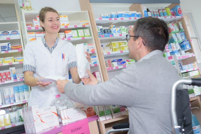 解释产品细节的女性化学家对药房的顾客 库存图片