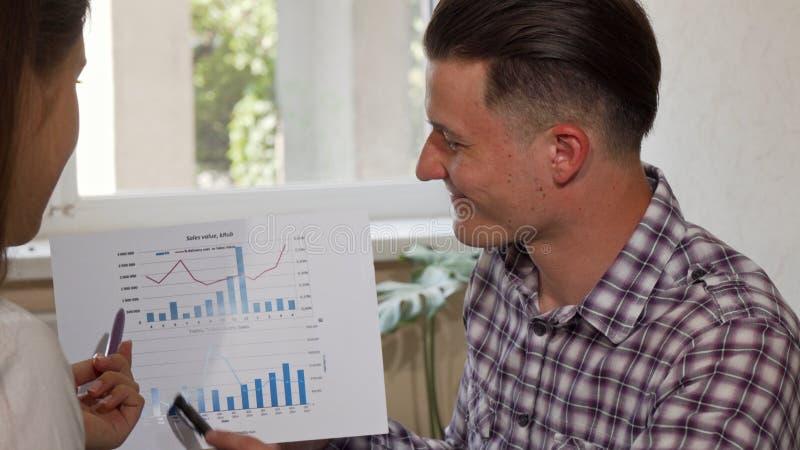 解释他的同事的快乐的年轻商人他的企业图 免版税库存图片