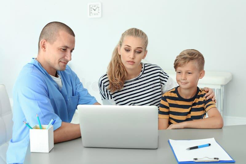 解释体检结果的男性医学助理对母亲和孩子 图库摄影