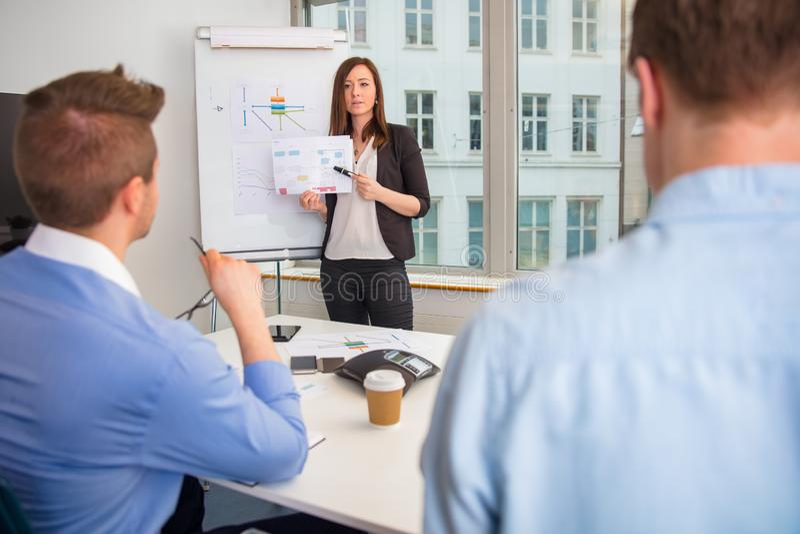 解释图的女实业家对同事在办公室 库存图片
