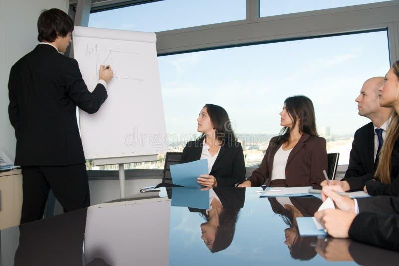 解释图表的商人在研讨会期间 免版税图库摄影