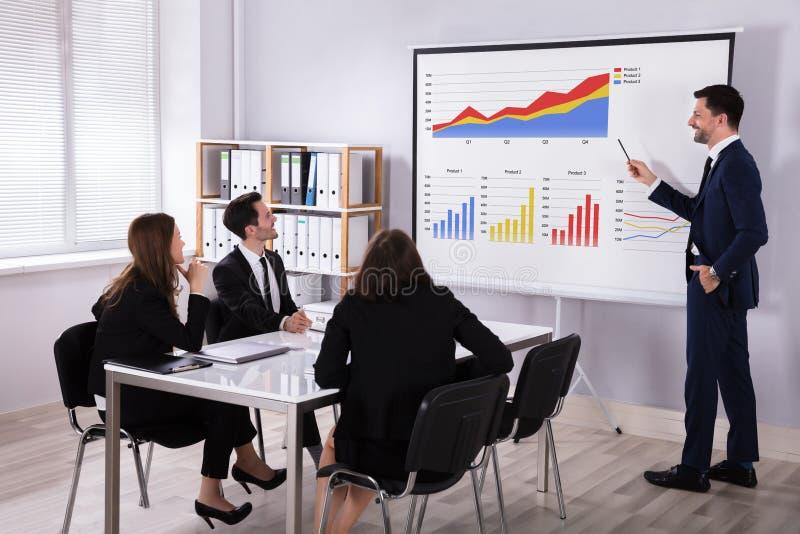 解释图表的商人对他的同事 免版税库存图片