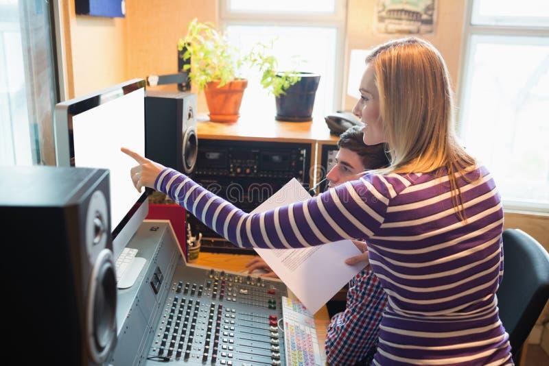 解释在显示器的女性雇员男性无线电主人 免版税库存图片