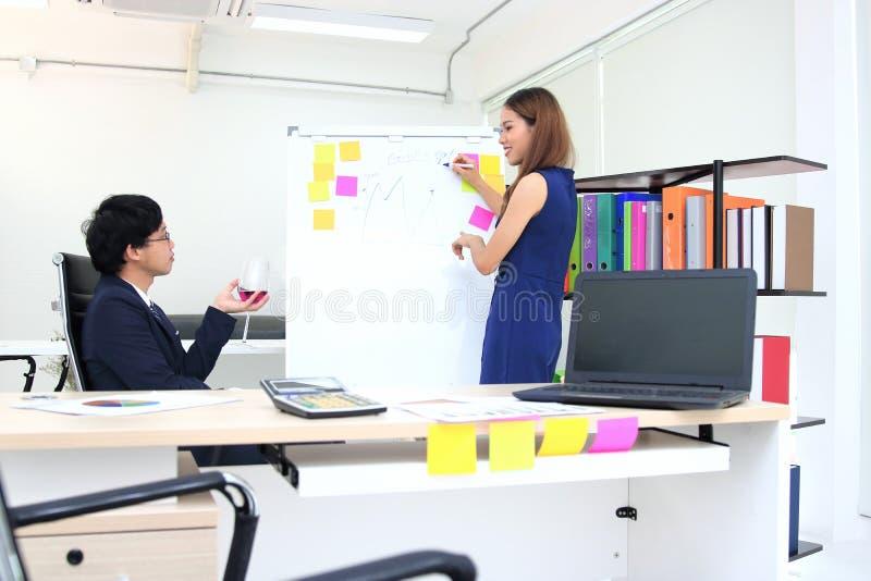 解释在活动挂图的确信的年轻亚裔女商人战略对上司在会议室里 免版税库存照片