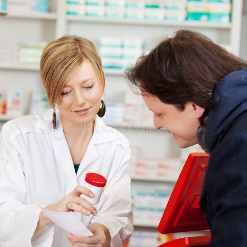 解释处方的药剂师对顾客 库存照片