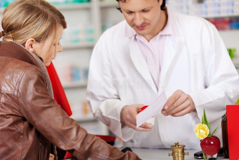 解释处方医学的药剂师对顾客 库存照片