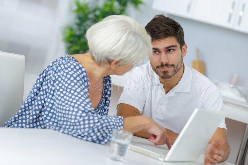 解释对年长妇女如何的年轻人使用膝上型计算机 免版税图库摄影