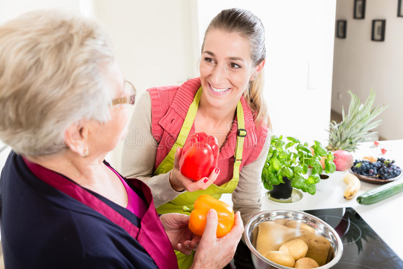 解释对甜椒的正确用途的婆婆在厨房t里 免版税库存图片