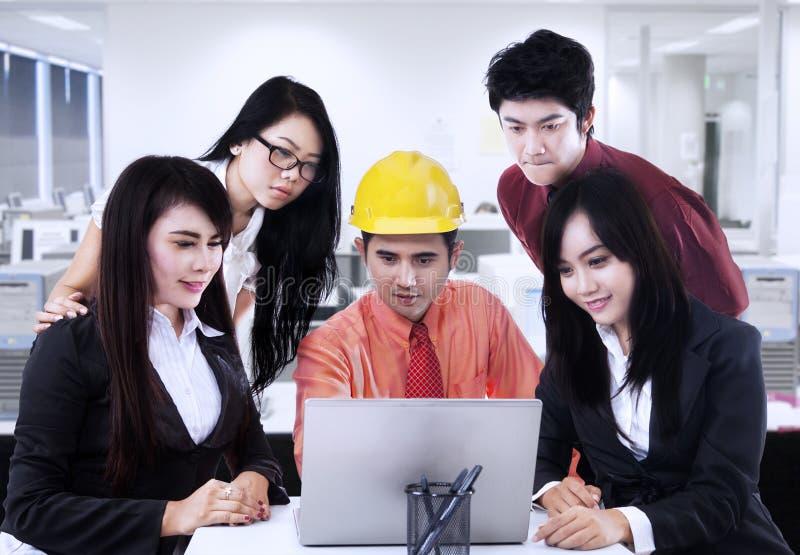 解释对队的亚裔承包商在办公室 免版税库存照片