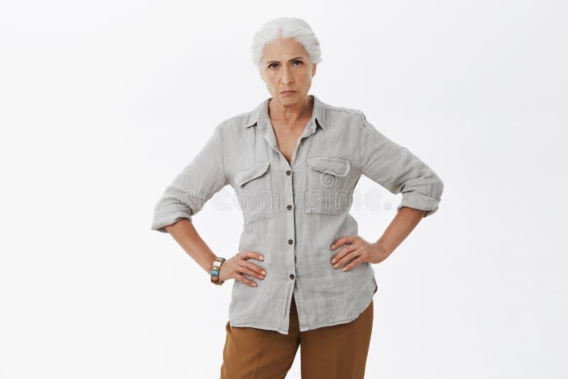 解释您行为年轻人 严密和失望的疯狂的老婆婆身分画象在生气的姿势的用交上 库存照片