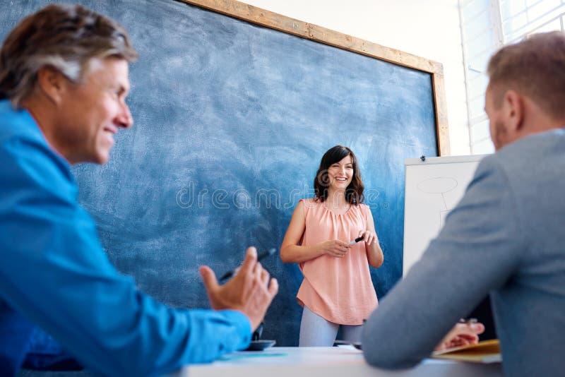 解释想法的微笑的年轻女实业家对whiteboard的工友 免版税库存图片