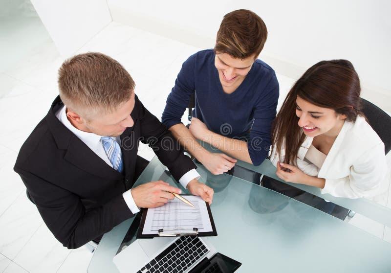 解释投资项目的财政顾问对夫妇 库存照片
