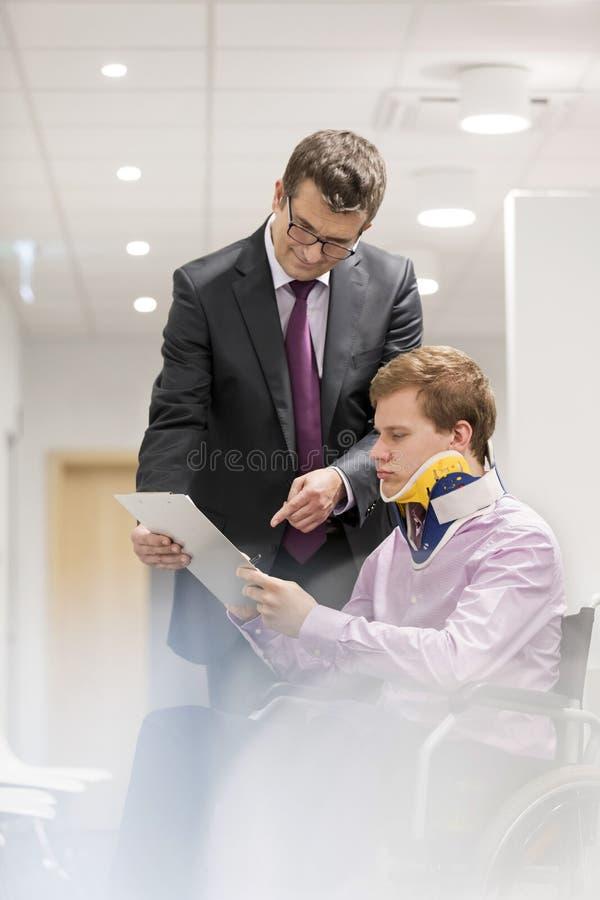 解释文件的医生对轮椅的残疾患者在医院 库存照片