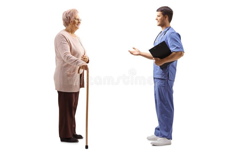 解释某事的男性医生对一名年长女性患者 免版税库存图片