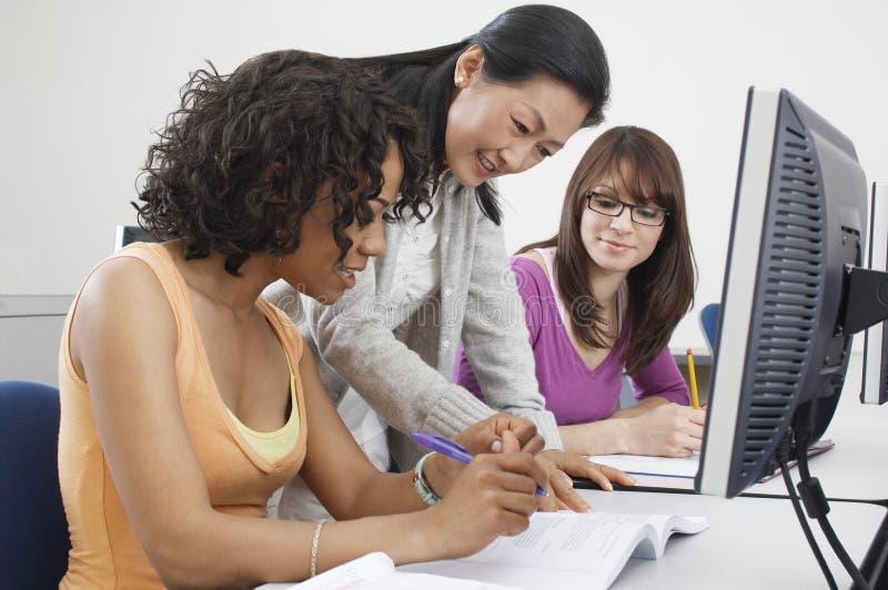 解释笔记的老师对女学生 免版税库存图片