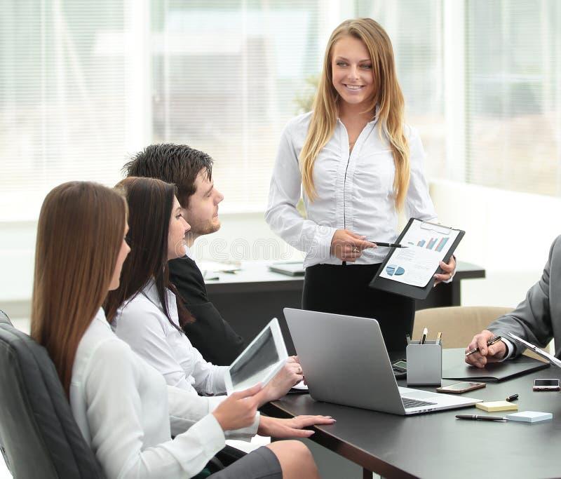 解释经营计划的女实业家对她的同事 免版税库存图片