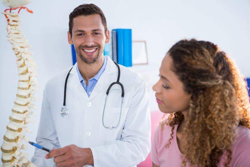 解释脊椎模型的生理治疗师对患者 免版税库存照片
