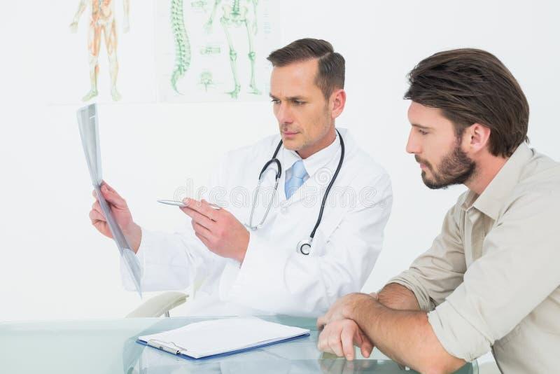 解释脊椎X-射线的男性医生对患者 库存图片